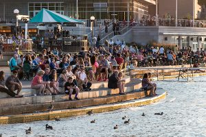 Terrace steps with people feeding ducks, dusk.