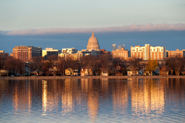 A shaft of late afternoon sunlight falls on the dome of the Wisconsin State Capitol and row of residential homes along the lakeshore of Monona Bay near the University of Wisconsin-Madison campus during autumn on Nov. 18, 2010.