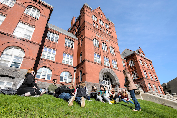 Teaching assistant Anke Keuser, standing, leads a discussion with her environmental studies capstone class outside in front of Science Hall at the University of Wisconsin–Madison during a sunny spring day.