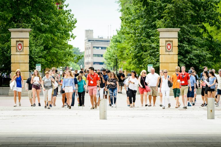 Student tour guides lead a group of visitors across campus.