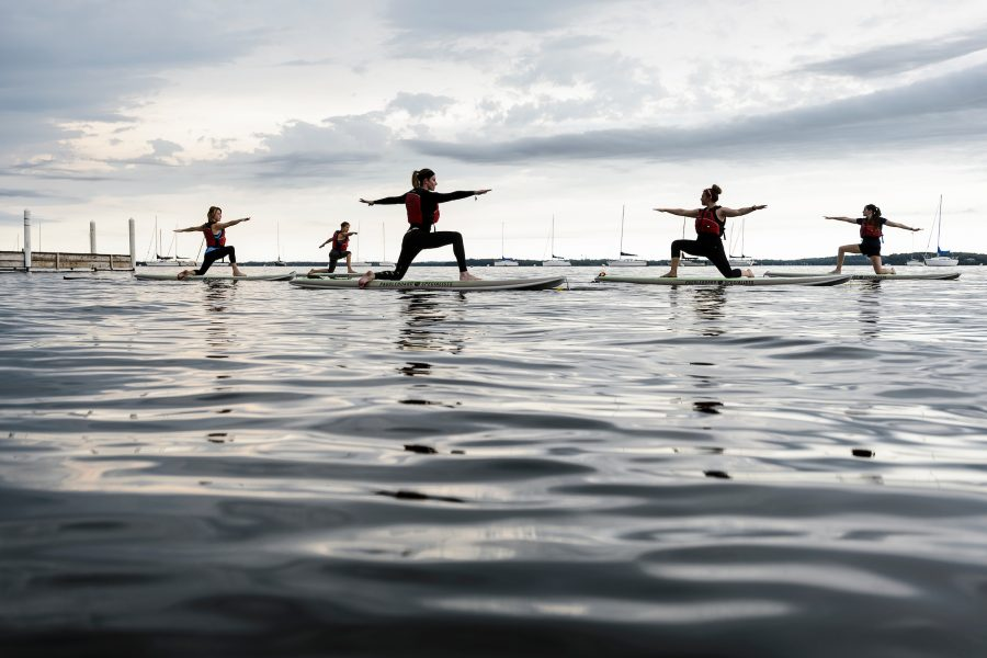 A group maintains balance during a standup paddleboard yoga class on Lake Mendota.