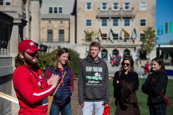 Student Tour guide showing prospective students and guests the Wisconsin State Historical Society while standing in Library Mall.